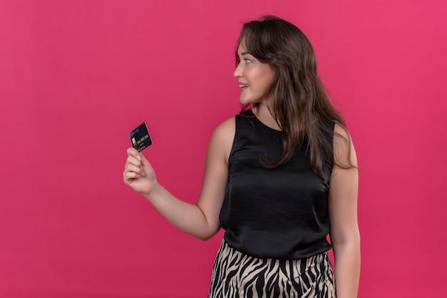 銀行カードを保持し、ピンクの壁に横を向いて黒いアンダーシャツを着て笑顔の女性