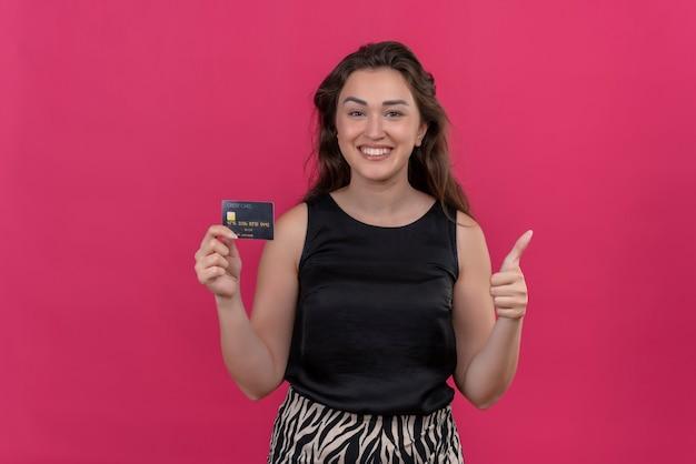 銀行カードを保持し、ピンクの壁に彼女を親指で黒のアンダーシャツを着て笑顔の女性