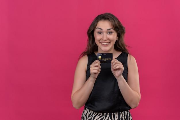 ピンクの壁に銀行カードを保持している黒いアンダーシャツを着て笑顔の女性