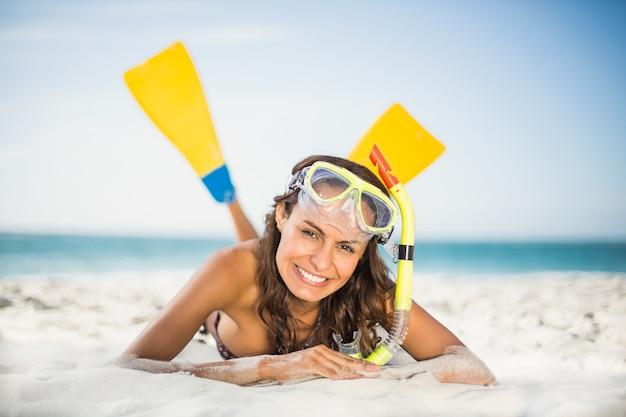 ビーチで足ひれを身に着けている笑顔の女性