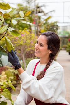 Smiling woman wearing gardening clothes and touching plants in greenhouse