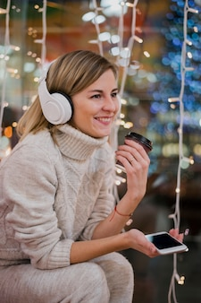 Smiling woman wearing headphones holding cup and phone near christmas lights