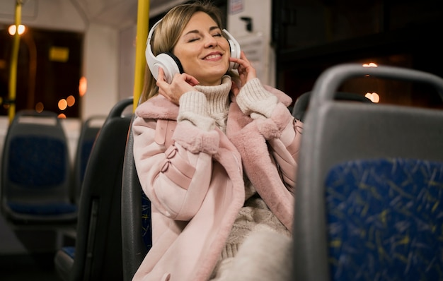 Smiling woman wearing headphones sitting in bus