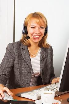 コンピューターを使用してヘッドフォンを着て笑顔の女性