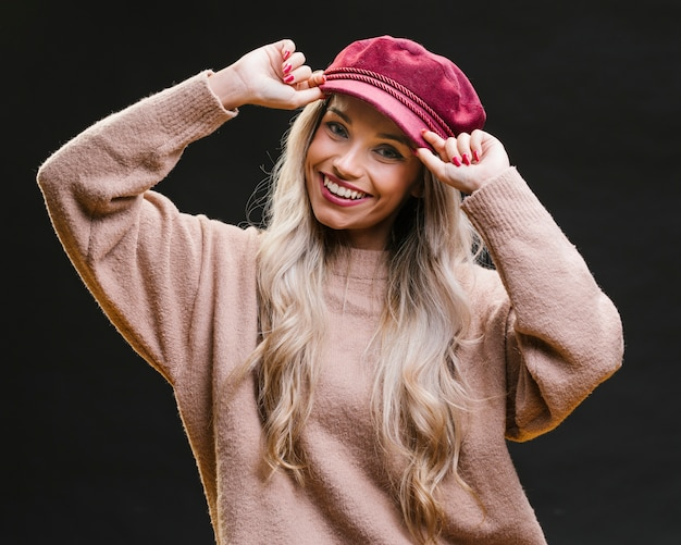 Smiling woman wearing pink cap and posing against black background