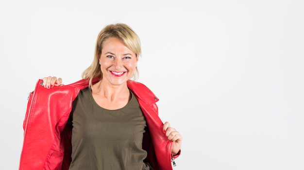 Smiling woman wearing red jacket looking at camera against white background
