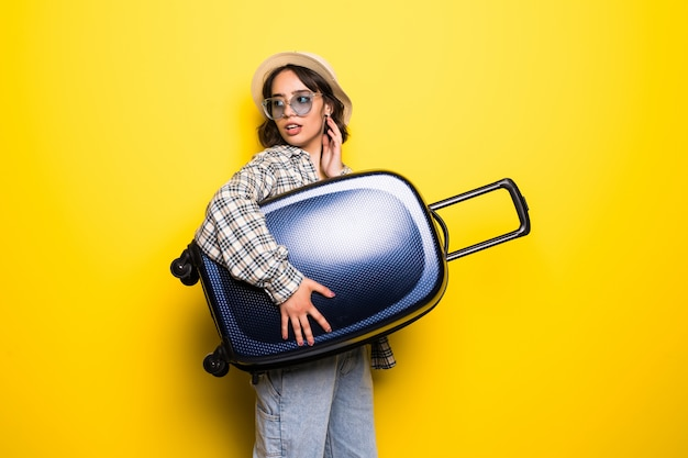 Donna sorridente che indossa occhiali da sole e cappello con la valigia isolato