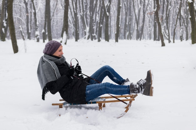 Smiling woman wearing a warm clothes sitting on sledge over the snowy landscape