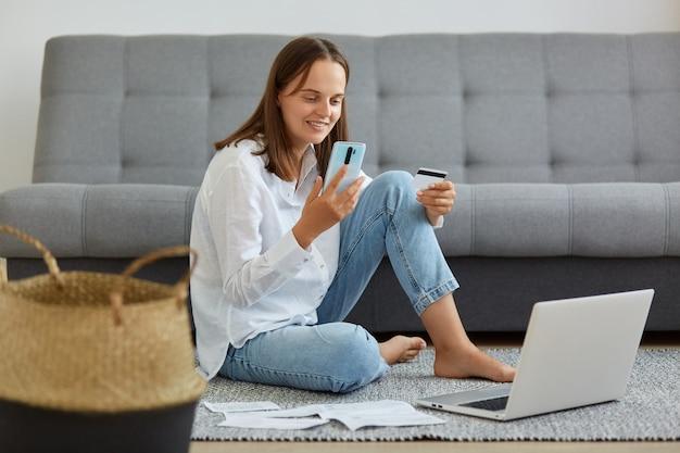 白いシャツとジーンズを着てソファの近くに座って、スマートフォンとクレジットカードを手に持って、オンラインで支払いをし、電話の画面を見ている笑顔の女性。