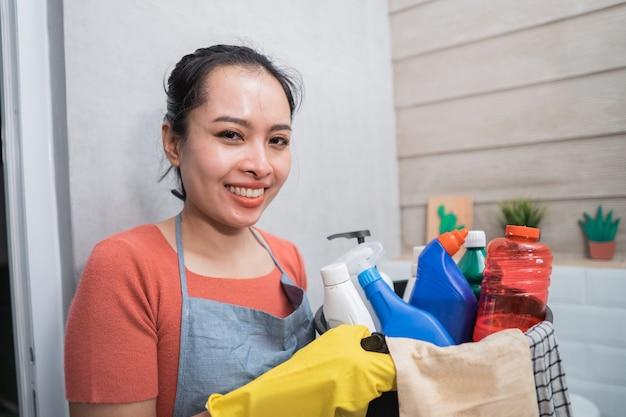 クリーニングツールとクリーニング液のボトルで満たされたバケツを運んで黄色い手袋を着用して笑顔の女性