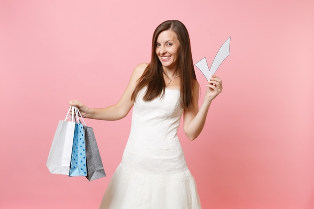 Smiling woman in white dress holding check mark, multi colored packages bags with purchases after shopping