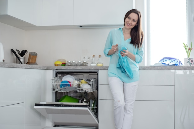 Smiling woman in white jeans and a turquoise shirt with a cup and a towel in her hands, standing next to an open dishwasher in a white interior kitchen set
