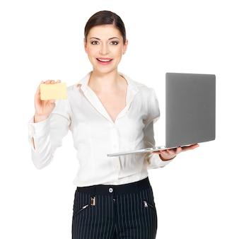 Donna sorridente in una camicia bianca con laptop e carta di credito isolato su bianco.