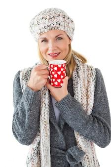 Smiling woman in winter fashion looking at camera with mug
