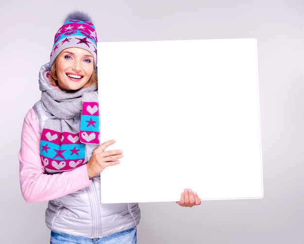 Smiling woman in winter outerwear holds the white placard in hands