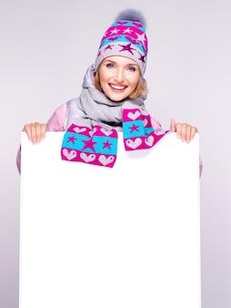 La donna sorridente in tuta sportiva invernale tiene il cartello bianco nelle mani