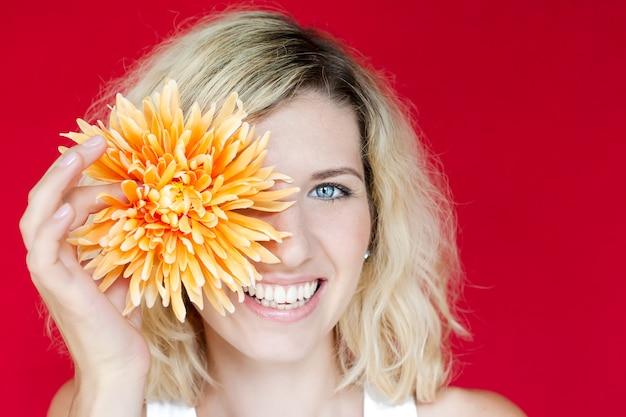 彼女の手に大きな花を持つ笑顔の女性