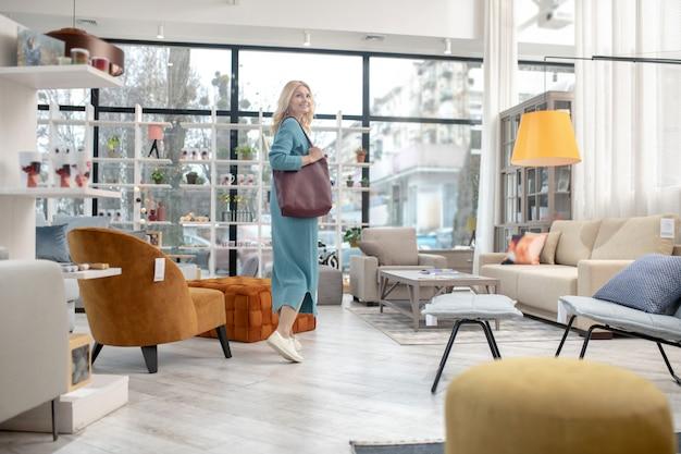 ブルゴーニュのバッグを肩にかぶった女性が笑顔で、家具店を歩いて、インテリアを見て、機嫌がいい。