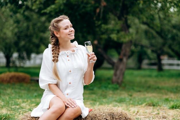 屋外で白ワインのグラスと笑顔の女性