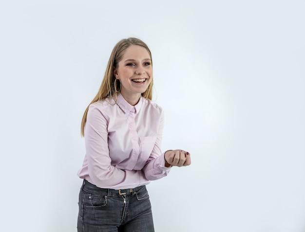 흰 벽 뒤에 서있는 셔츠와 함께 웃는 여자