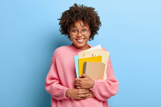 Smiling woman with an afro posing in a pink sweater