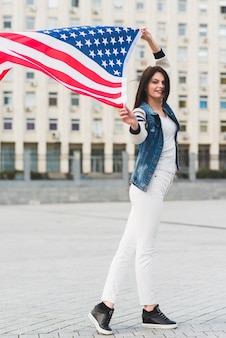 Smiling woman with american flag in city