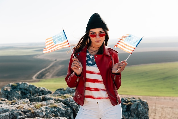 Smiling woman with american flags posing on top of mountain