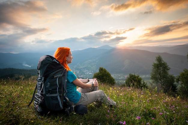 Smiling woman with backpack sitting in the grass with wild flowers on a hill and looking over the mountains