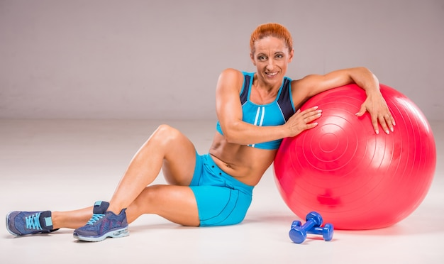 Smiling woman with ball and dumbbells.