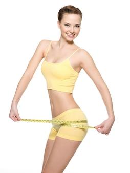 白で隔離され、ダイエット後の測定タイプで太ももを測定する美しいボディを持つ女性の笑みを浮かべてください。