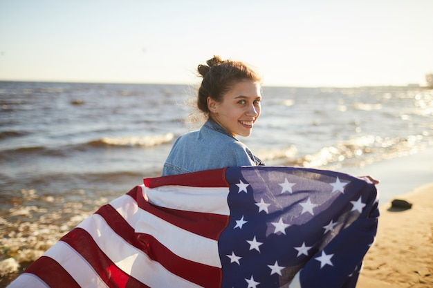 Smiling woman with big national flag