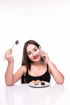 La donna sorridente con capelli neri e le labbra rosse assaggia i rotoli di suushi che tengono le bacchette di legno in sua mano che parla sul suo telefono