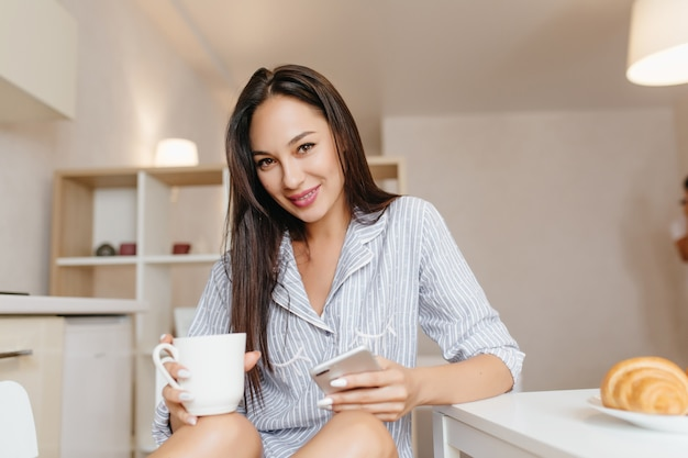 Smiling woman with black hair sitting in kitchen with smartphone during breakfast