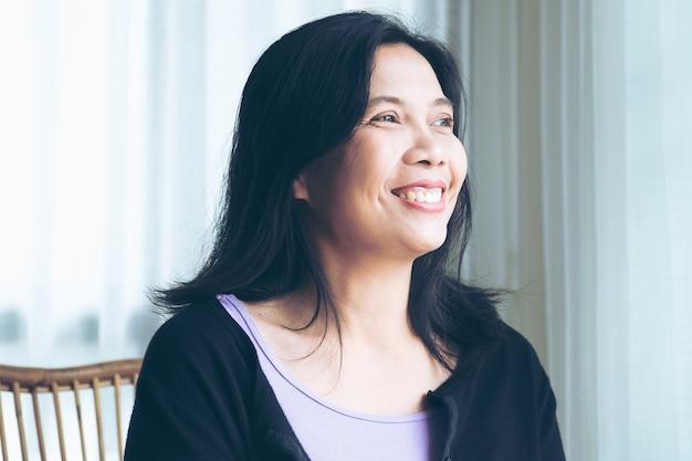 屋内に座っている黒い長い髪の笑顔の女性