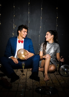 Smiling woman with bottle near happy man with balloon near glasses