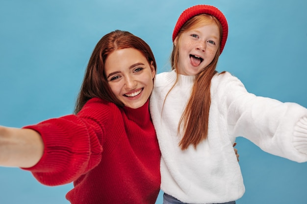 Smiling woman with brunette hair in red sweater hugs her young ginger sister in fashionable outfit on isolated wall
