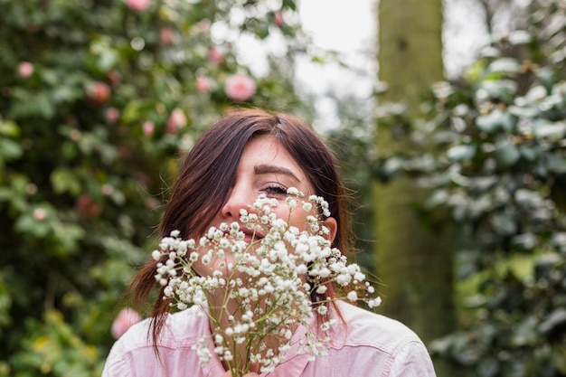 Smiling woman with bunch of plants near pink flowers growing on bushes