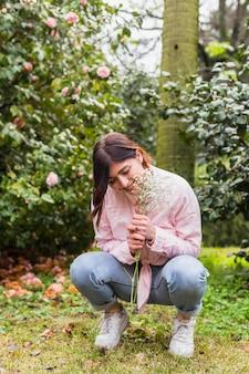 La donna sorridente con il mazzo di piante si avvicina ai fiori rosa che crescono sui ramoscelli verdi