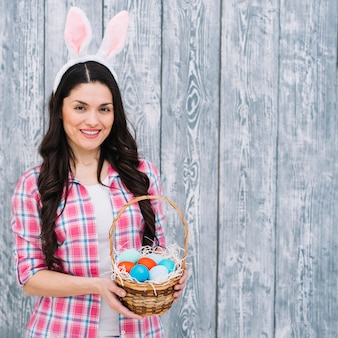 Smiling woman with bunny ears on head showing easter eggs basket against wooden backdrop