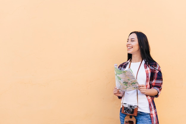 Smiling woman with camera around her neck holding map