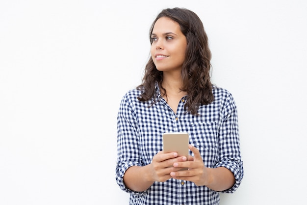 Smiling woman with cell phone looking aside
