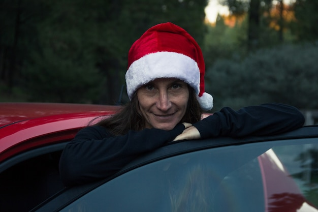 Smiling woman with christmas hat leaning on door of red car middle aged lady ready for ride