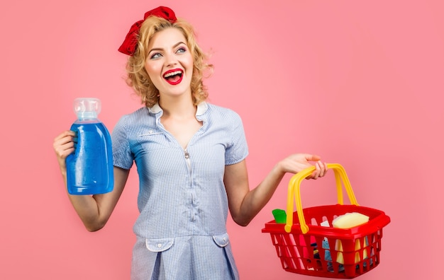 Smiling woman with cleaning products. female cleaner holds basket with cleaning supplies. house chores.