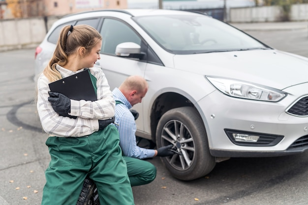Smiling woman with clipboard and worker changing wheel of a car