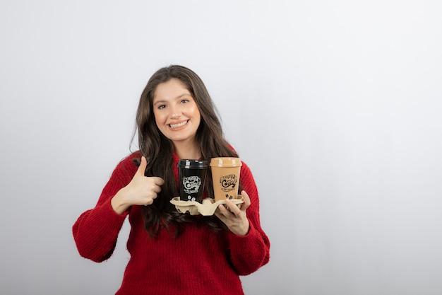 엄지손가락을 보여주는 판지 홀더에 커피 컵 웃는 여자.