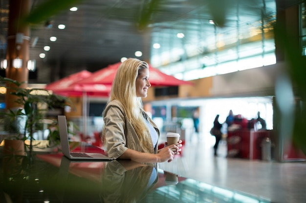 Smiling woman with coffee standing in waiting area