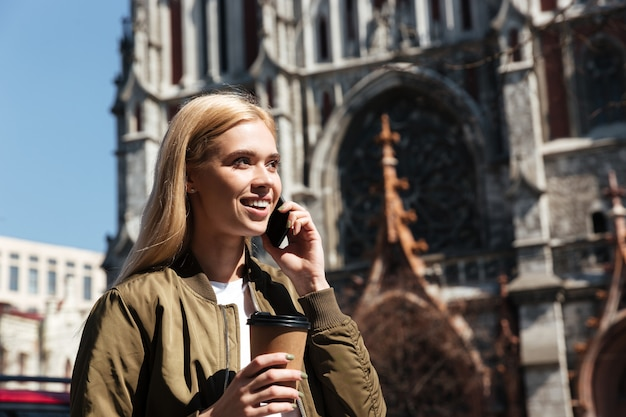 Smiling woman with coffee talking on smartphone