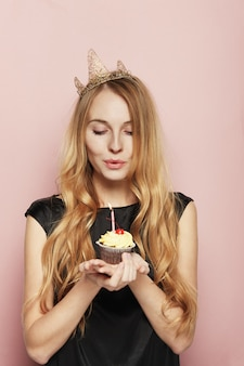Smiling woman, with a crown, holding a birthday cupcake