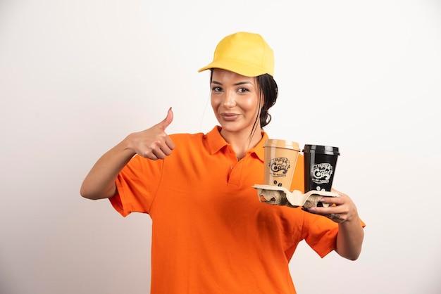 親指を上に表示カップと笑顔の女性