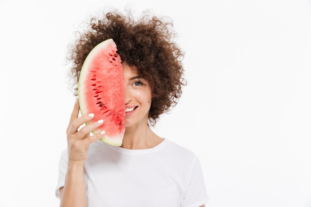 Smiling woman with curly hair holding slice of a watermelon